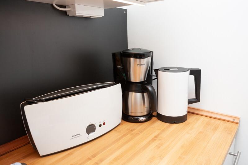 Die Küche ist mit einem Toaster, einem Wasserkocher und einer Kaffeemaschine ausgerüstet. / The kitchen is equipped with a toaster, a water heater and a coffee machine.